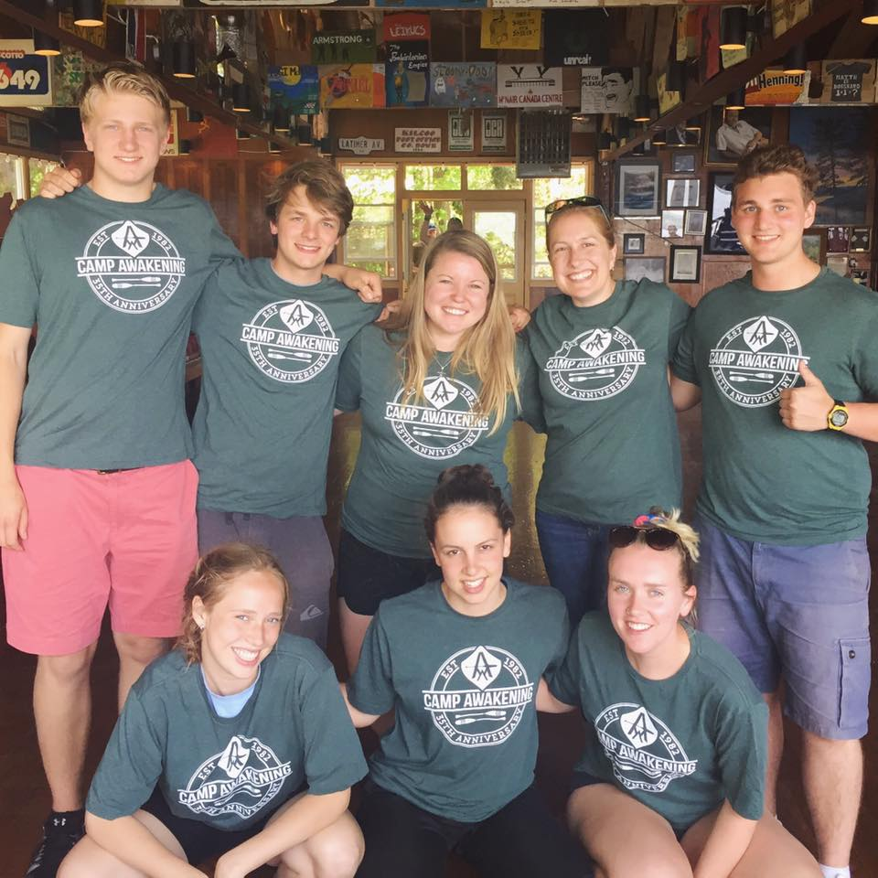 Group photo of summer camp staff in matching green Camp Awakening t-shirts