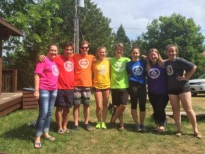 Group photo of Camp Awakening staff members wearing a rainbow of coloured t-shirts with the camp logo