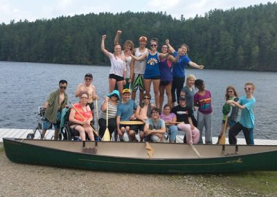 Group photo of campers and staff posed in front of one of Camp Awakening's iconic green canoes after completing a wilderness canoe trip in Algonquin Park