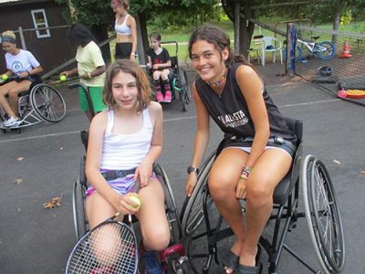 Smiling camper and staff member posing in sport wheelchairs during a game of tennis